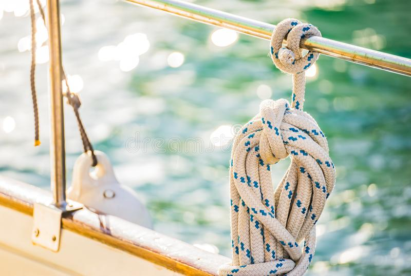 Nautical rope tied on railing of boat deck, yachting stock image