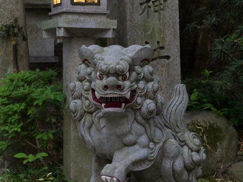 Close up Komainu dog-lionstone statue at the Shrine in Japan. royalty free stock image