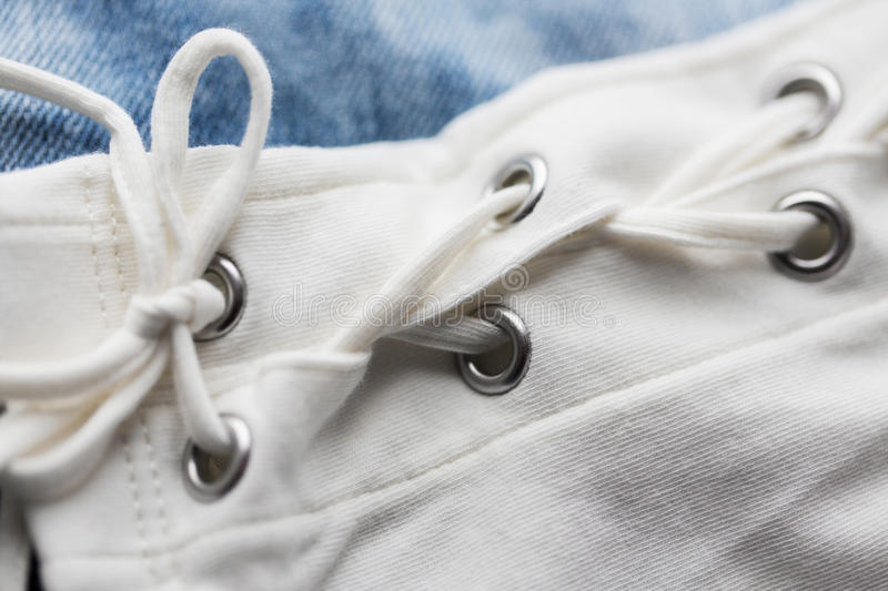Close up of lacing on clothing item. Clothes, fashion and objects concept - close up of lacing on clothing item royalty free stock photography