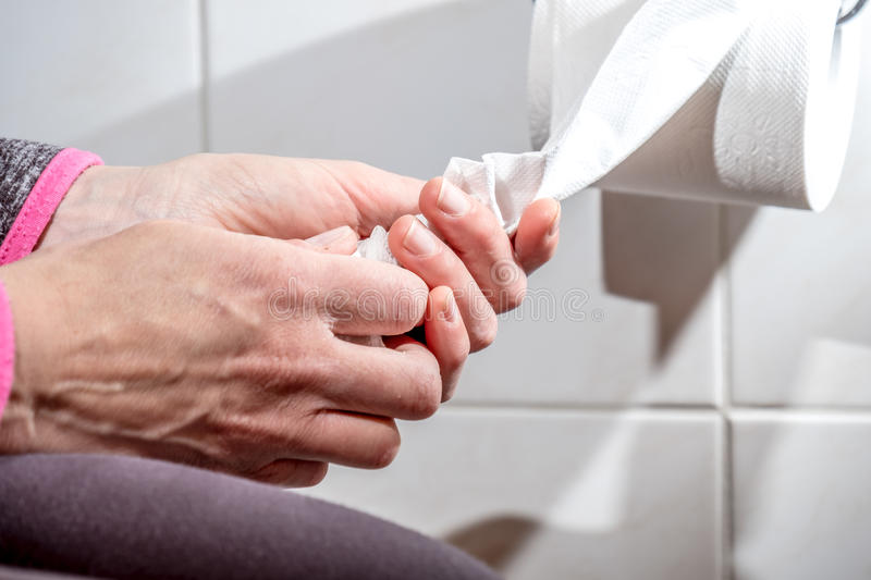 Close-up Of A lady`s Hand Using Toilet Paper stock image