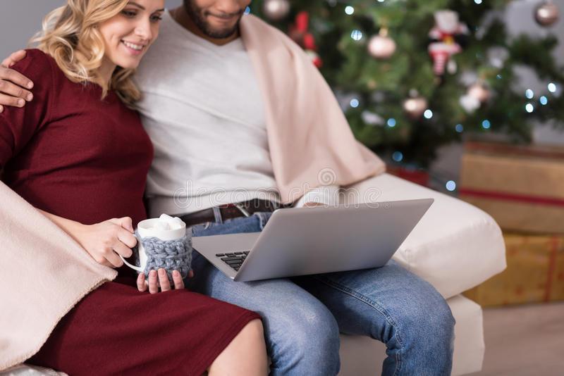 Close up of the laptop being used by happy couple royalty free stock photography