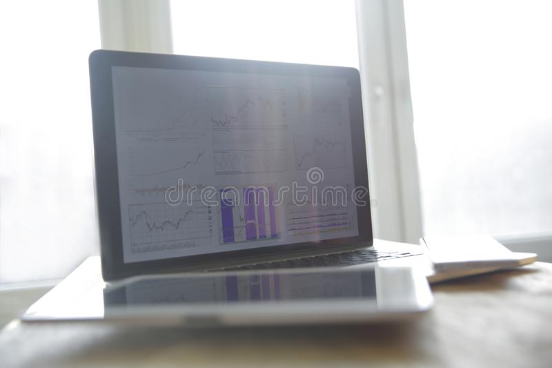 Close up of laptop with business chart on screen place on office desktop. Forex and finance concept stock images