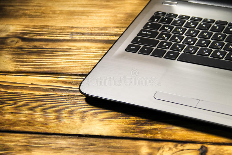 Close-up of laptop keyboard on wooden desk royalty free stock photo