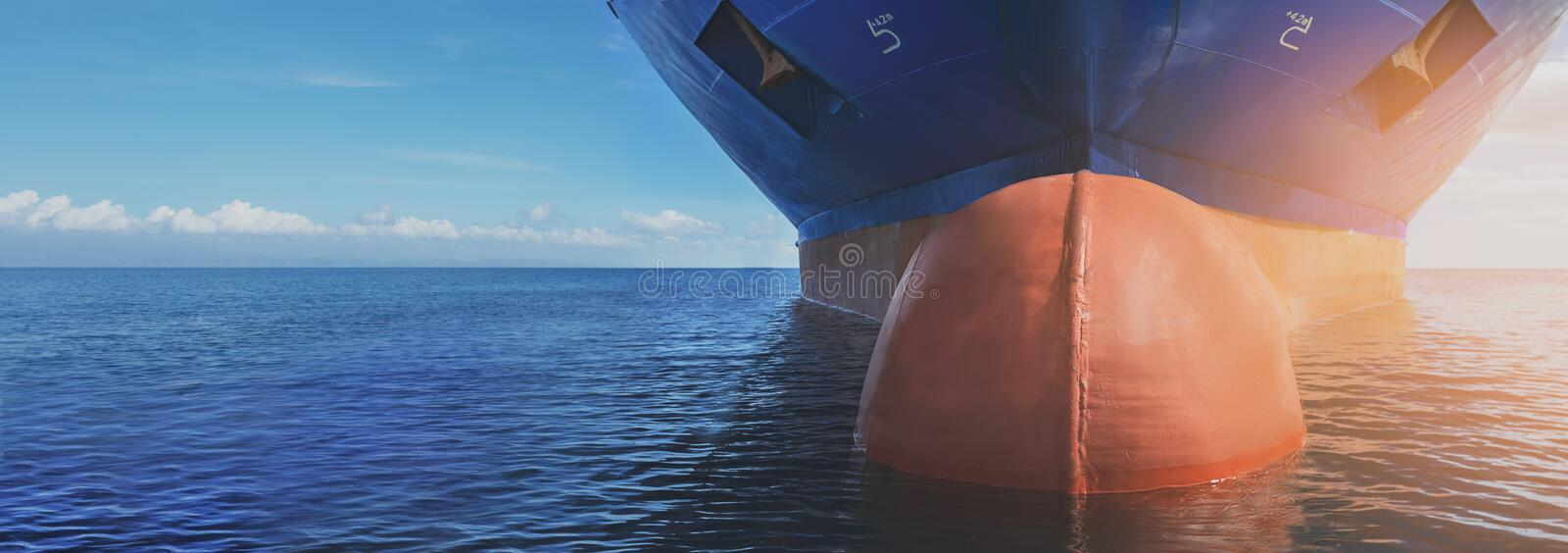 Close up of large blue merchant crago ship in the middle of the ocean underway. Performing cargo export and import operations. With sun rays, horizon line and royalty free stock images