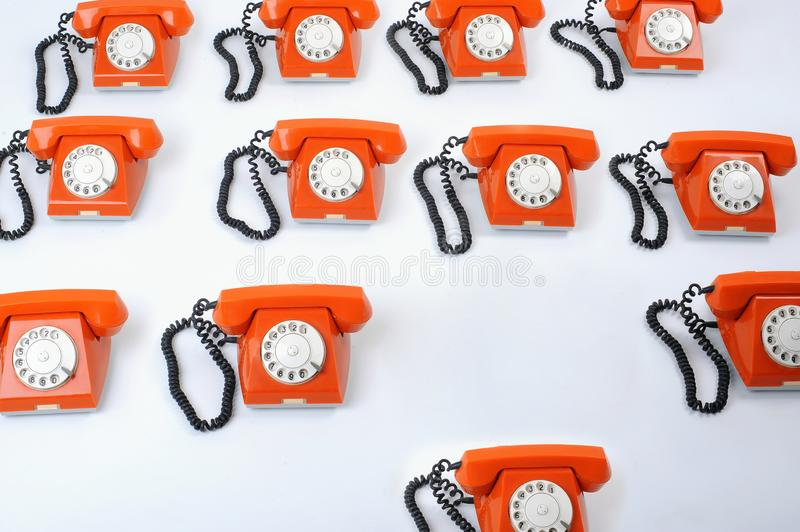 Close up of a large group of orange rotary telephones stock photo
