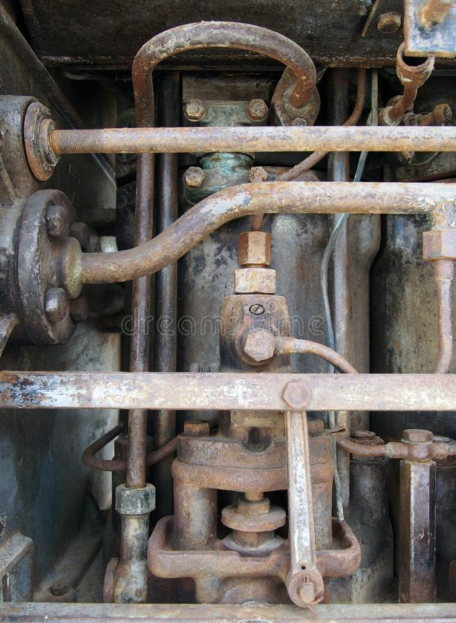 Close up of a large old abandoned marine diesel engine showing rusting pipes and cylinders and bolts royalty free stock image