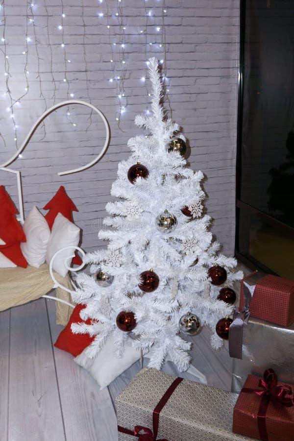 Close-up largo de um ornamento glittery vermelho em uma árvore de Natal artificial branca em um armazém Borrão raso do foco Bangu foto de stock royalty free