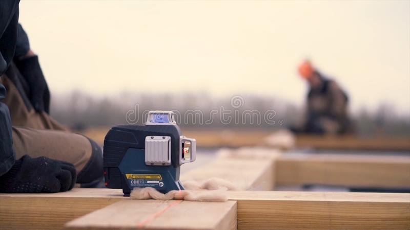 Close up of laser measurement level for construction works standing on a wooden bar at the construction site. Clip. Male royalty free stock image