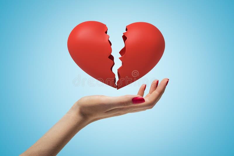 Close up lateral da mão da mulher que enfrenta acima e que levita o coração quebrado vermelho em claro - fundo azul do inclinação imagens de stock