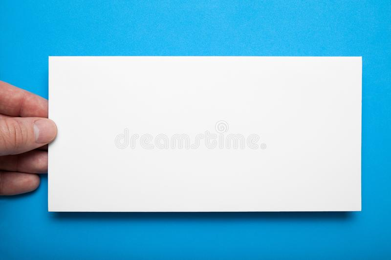 Close-up, layout DL flyer in hand on a blue background.  royalty free stock photos