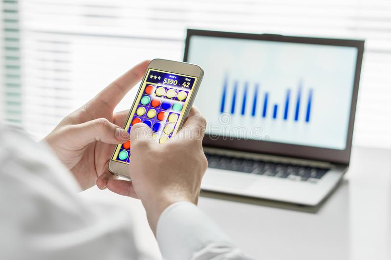 Close up of Lazy and unproductive office worker. Close up of Lazy and unproductive office worker playing mobile game with smart phone during business hours stock photos