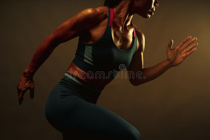 Close up of lean healthy core muscle of athletic asian woman sprint running to the finish line with warm light from the right, stock images