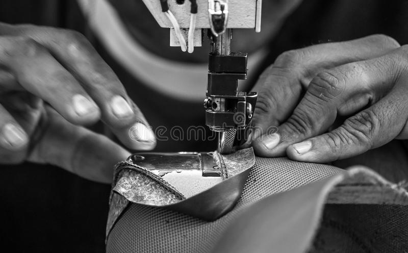 Close up of Leather sewing machine in action in a workshop with hands working in black and white. Close up of Leather sewing machine in action in a workshop in royalty free stock photo