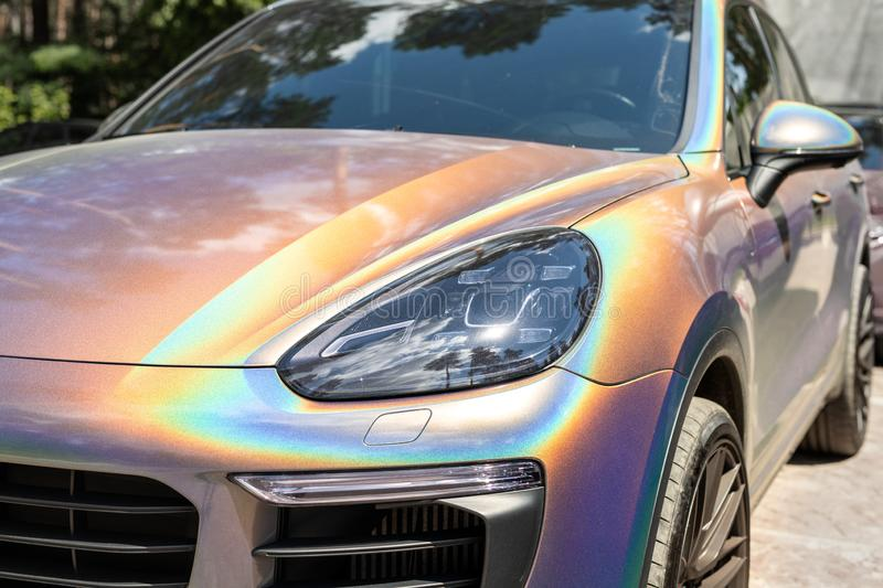 Close-up LED headlight expensive car part with exclusive iridescent painting. Vehicle covered with vibrant chameleon. Film stock image