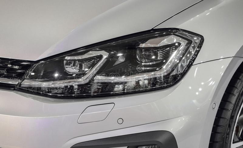 The close up of left headlight of gray metallic sport car. stock photography