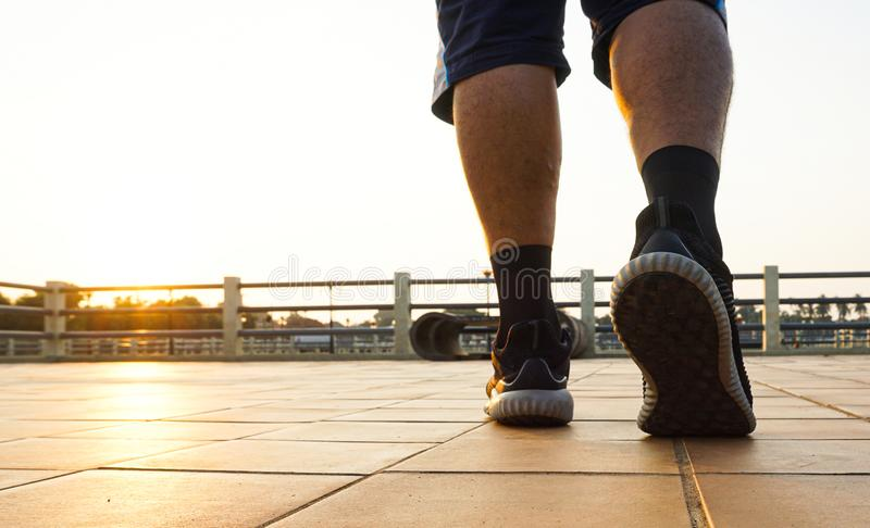 Close up legs and black shoes of  runner man running with sprint on the road during sunrise. stock photos
