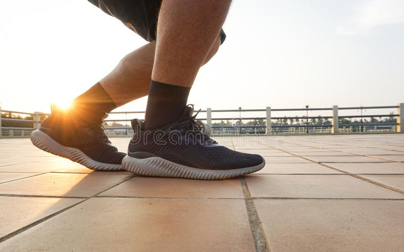Close up legs and black shoes of runner man running with sprint on the road during sunrise. royalty free stock image