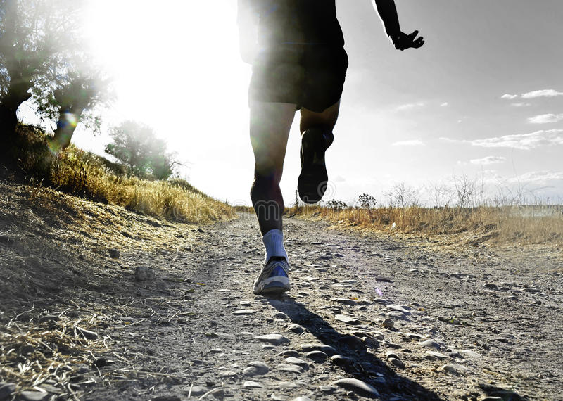 Close up legs and feet of extreme cross country man running and training on rural track jogging at sunset royalty free stock photography