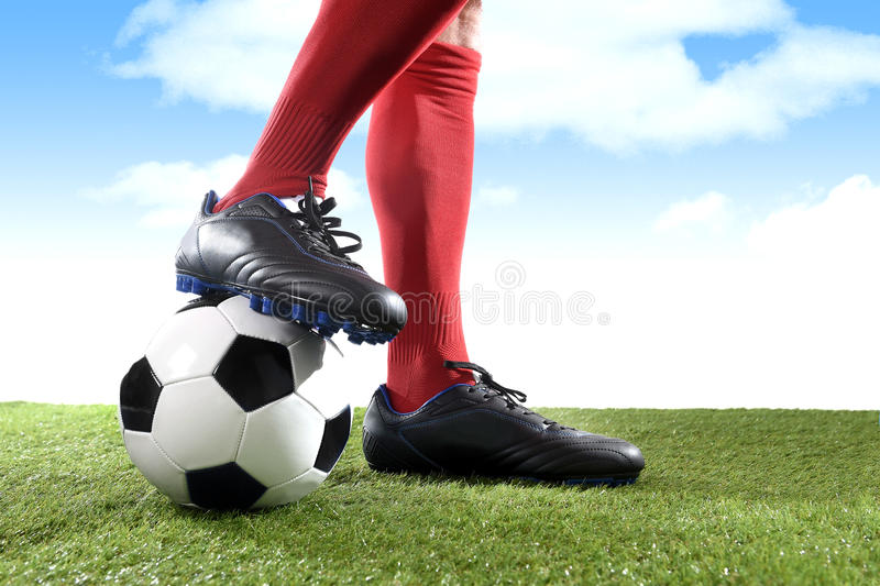 Close up legs feet football player in red socks and black shoes playing with ball on grass pitch outdoors stock photos