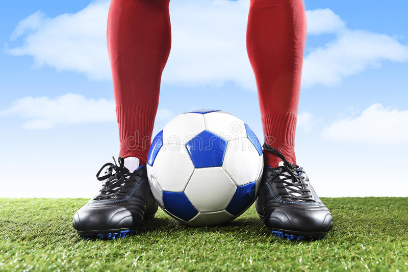 Close up legs feet football player in red socks and black shoes playing with ball on grass pitch outdoors stock images