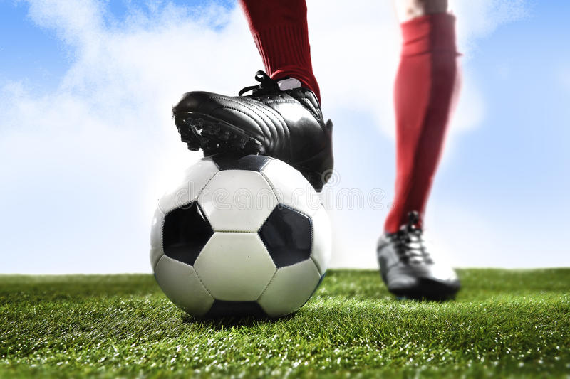 Close up legs feet football player in red socks and black shoes playing with ball on grass pitch outdoors stock photography