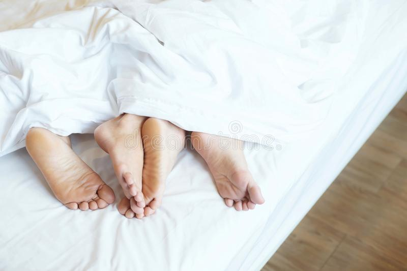 Close up legs feet of two Lovers couple sleeping side by side embracing under blanket white sheets in bed at home on holiday conc royalty free stock photography