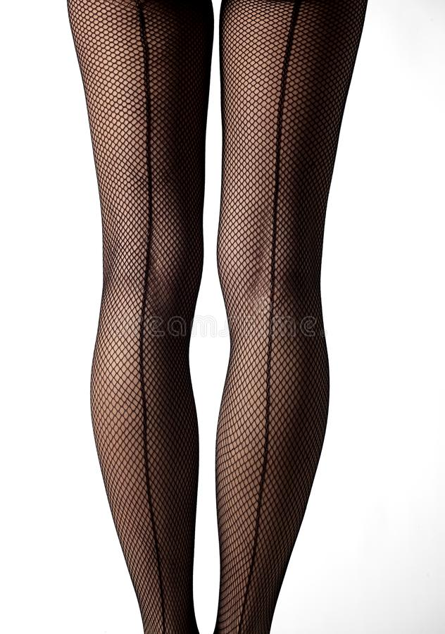 Close-up of legs with fishnet stockings and back line royalty free stock image