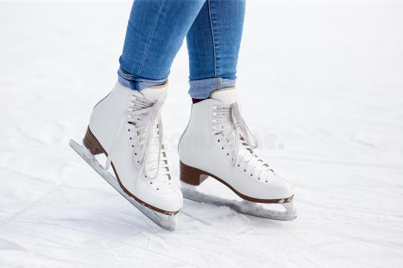Close up of legs in leather skates over white ice at rink royalty free stock image