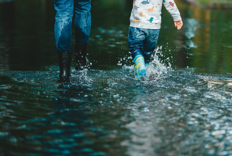 Close-up legs of mothers and son in the summer puddles. Rear view stock image