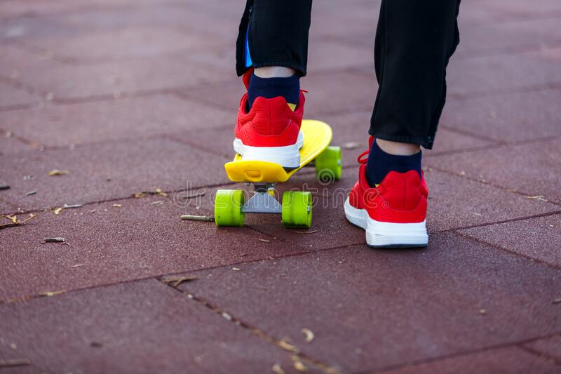 Close up legs in red sneakers riding on yellow skateboard in motion. Active urban lifestyle of youth, training, hobby, activity. Concept. Active outdoor sport stock image