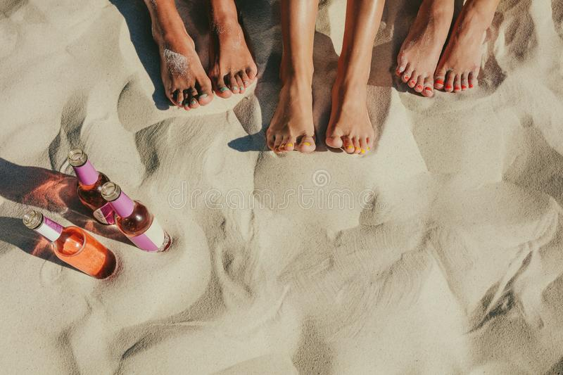 Close up of legs of three women beside bottles of soft drinks at. Close up shot of legs of three women sitting on beach sand with nails painted in different stock photos