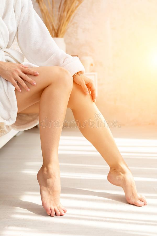 Close-up of legs of woman in white terry bathrobe on bed with ideal figure in light room. royalty free stock image