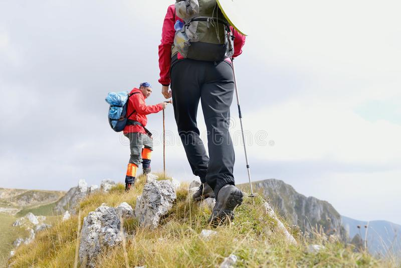 Close-up of legs of young hikers walking on the country path. Young couple trail waking. Focus on hiking shoes stock photography