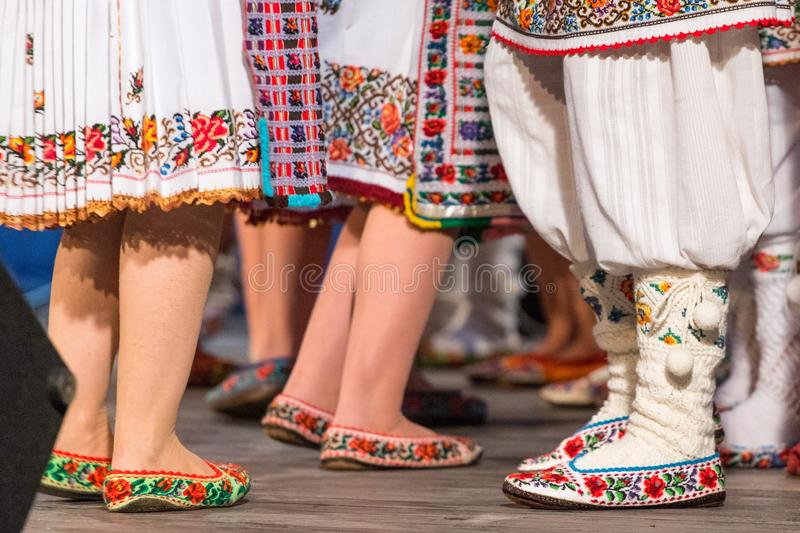 Close up of legs of young Romanian dancers perform a folk dance in traditional folkloric costume. Folklore of Romania royalty free stock images
