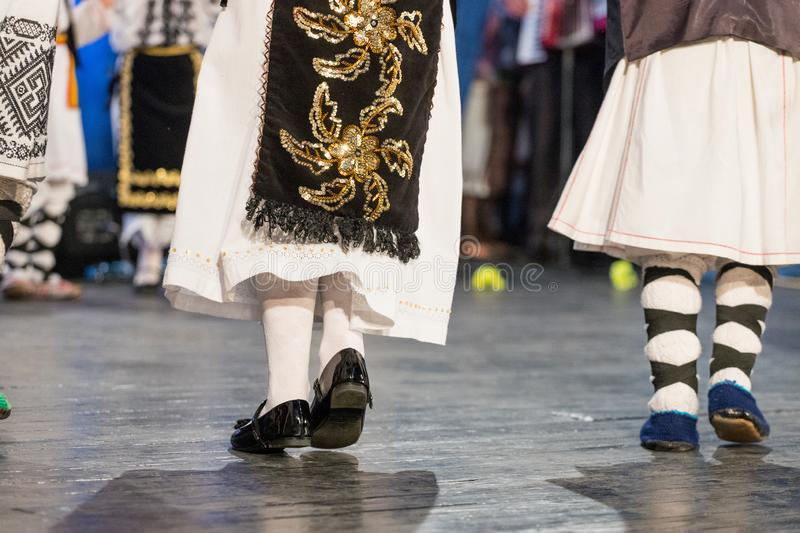 Close up of legs of young Romanian dancers perform a folk dance in traditional folkloric costume. Folklore of Romania royalty free stock photography