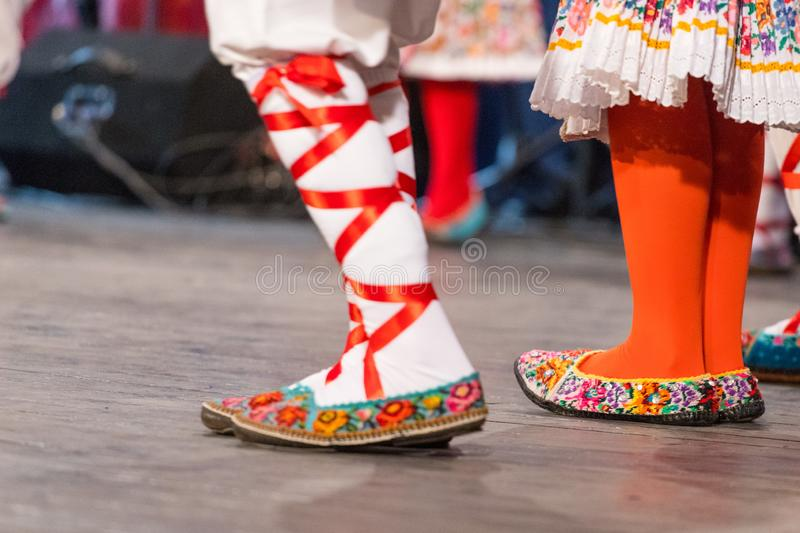 Close up of legs of young Romanian dancers perform a folk dance in traditional folkloric costume. Folklore of Romania.  stock photos