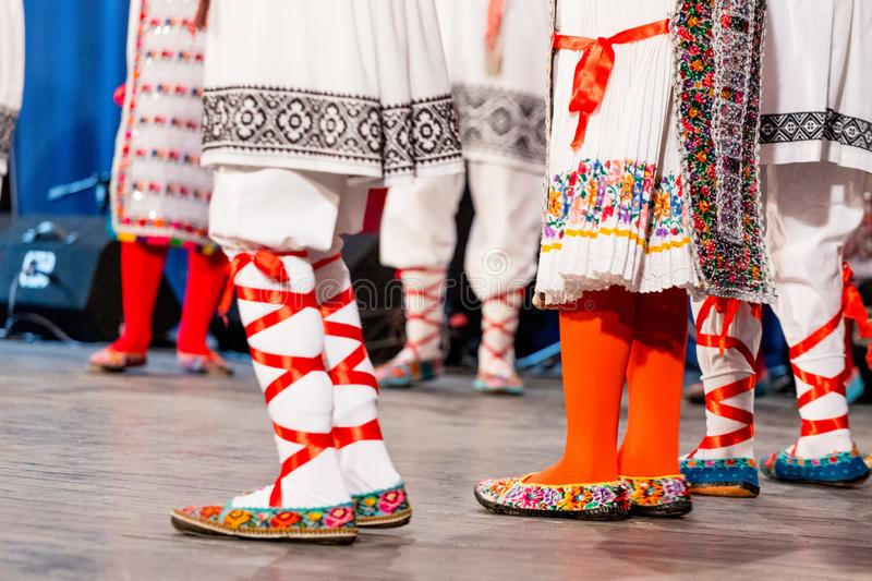 Close up of legs of young Romanian dancers perform a folk dance in traditional folkloric costume. Folklore of Romania.  royalty free stock images