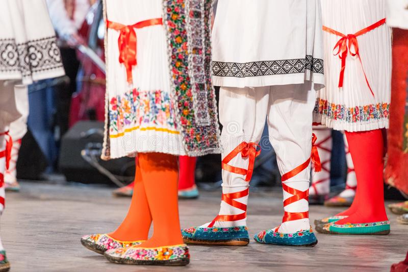 Close up of legs of young Romanian dancers perform a folk dance in traditional folkloric costume. Folklore of Romania stock photography