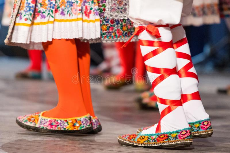 Close up of legs of young Romanian dancers perform a folk dance in traditional folkloric costume. Folklore of Romania.  stock image