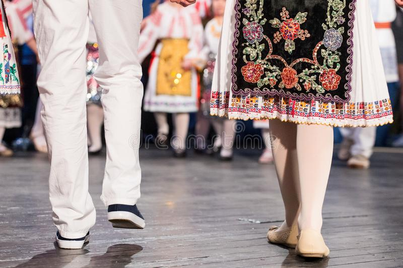 Close up of legs of young Romanian dancers perform a folk dance in traditional folkloric costume. Folklore of Romania royalty free stock image