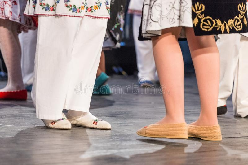 Close up of legs of young Romanian dancers perform a folk dance in traditional folkloric costume. Folklore of Romania royalty free stock photos