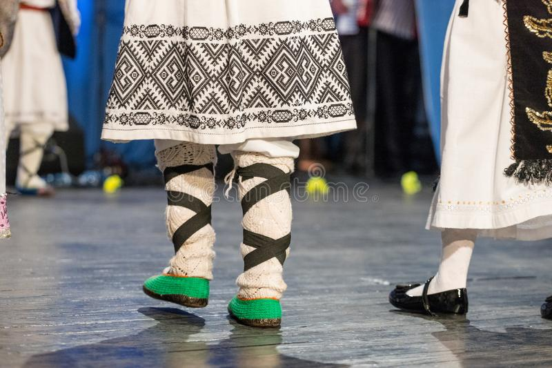 Close up of legs of young Romanian dancers perform a folk dance in traditional folkloric costume. Folklore of Romania stock photos
