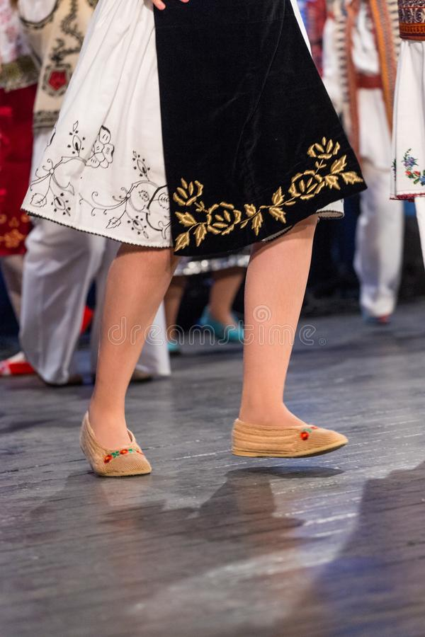 Close up of legs of young Romanian dancers perform a folk dance in traditional folkloric costume. Folklore of Romania.  stock photography