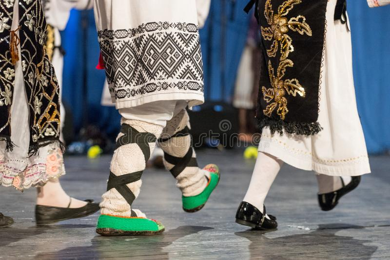 Close up of legs of young Romanian dancers perform a folk dance in traditional folkloric costume. Folklore of Romania.  stock photo