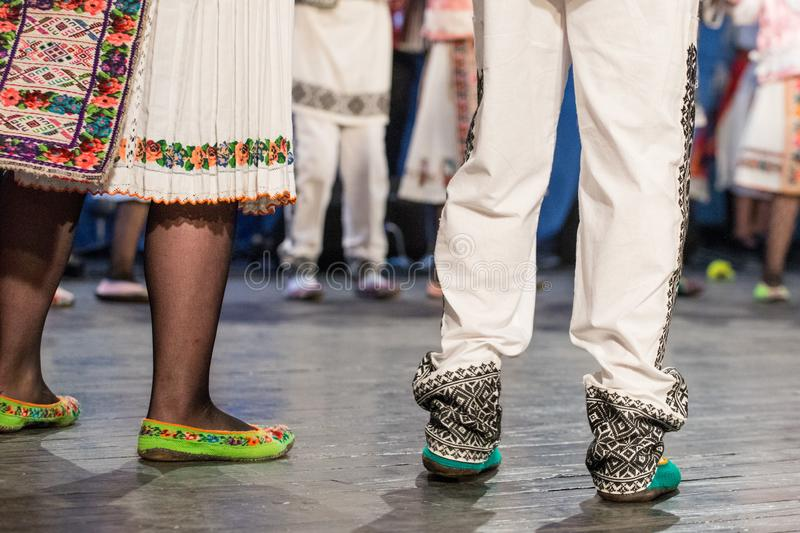 Close up of legs of young Romanian dancers perform a folk dance in traditional folkloric costume. Folklore of Romania.  royalty free stock photography