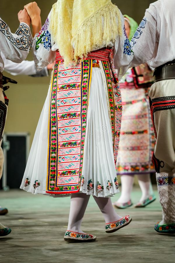 Close up of legs of young Romanian female dancer in traditional folkloric costume. Folklore of Romania royalty free stock photography
