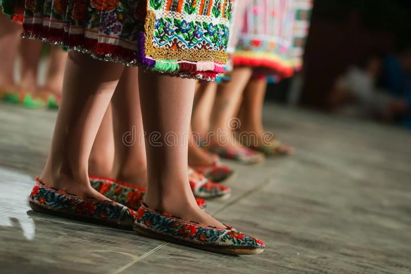 Close up of legs of young Romanian female dancers in traditional folkloric costume. Folklore of Romania royalty free stock image