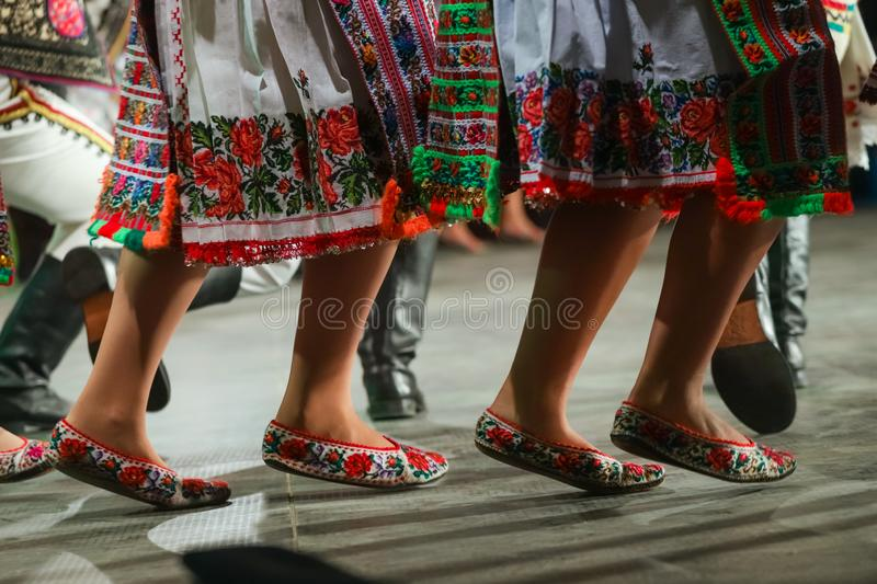Close up of legs of young Romanian female dancers in traditional folkloric costume. Folklore of Romania royalty free stock photography
