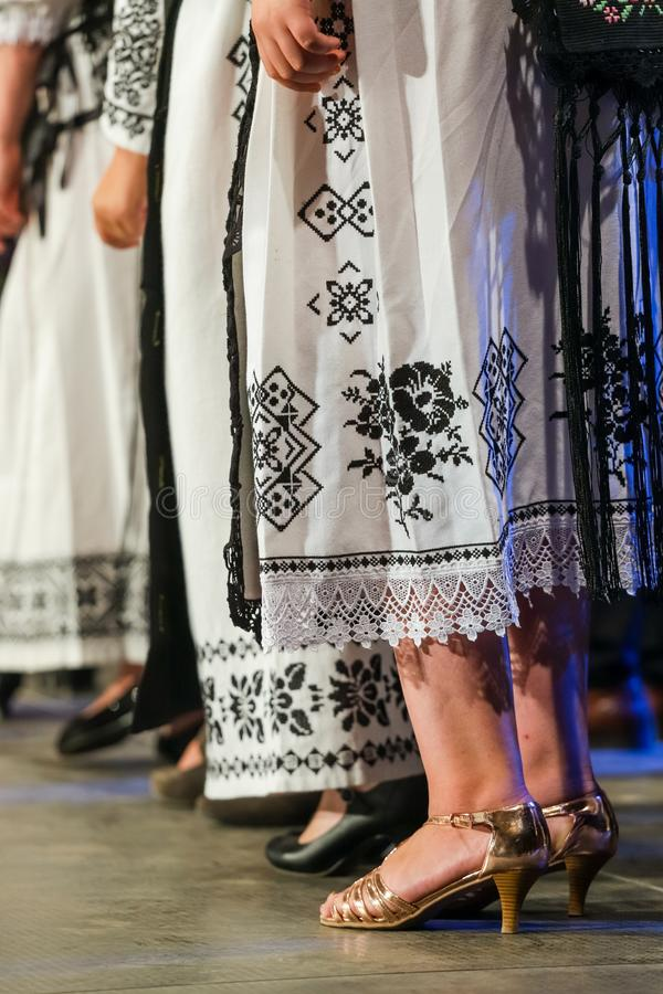 Close up of legs of young Romanian female dancers in traditional folkloric costume. Folklore of Romania stock photography