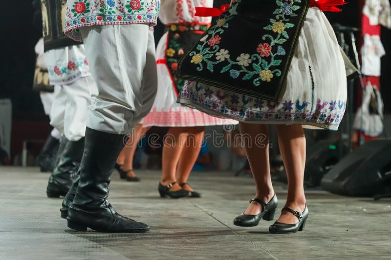 Close up of legs of young Romanian female and male dancers in traditional folkloric costume. Folklore of Romania royalty free stock photos